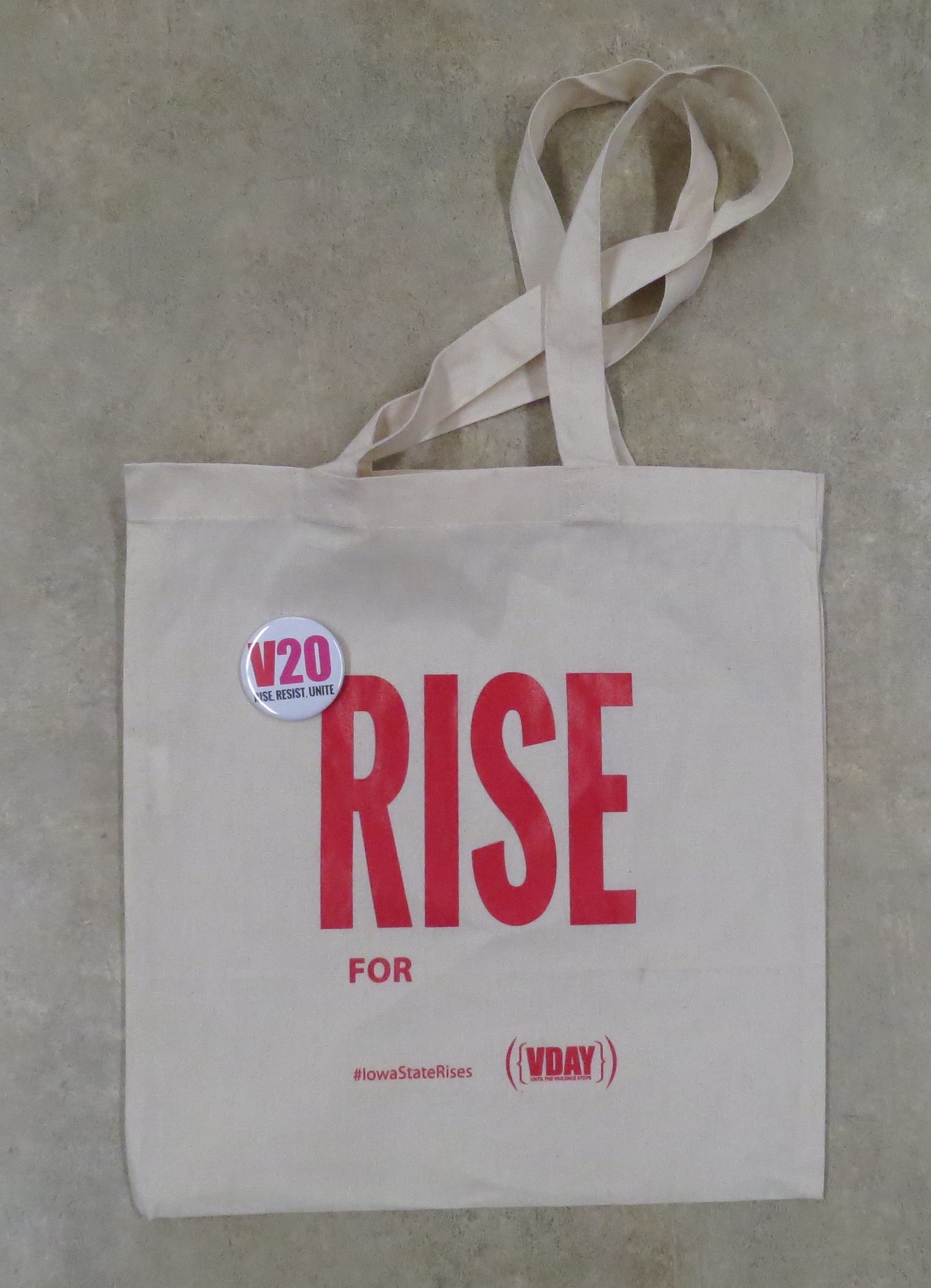 "White tote with ""Rise For"" text in red"