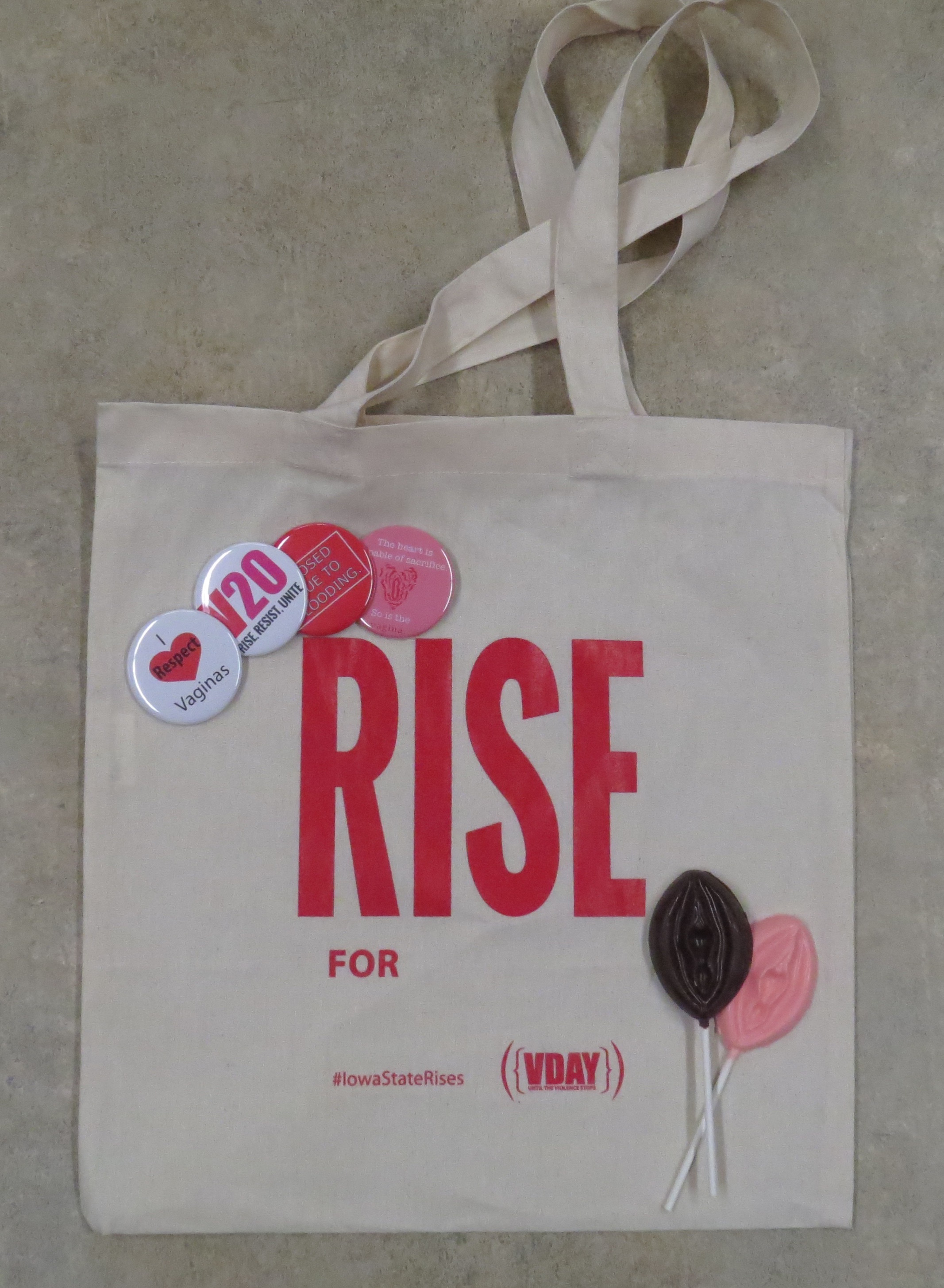 "White tote bag with words ""Rise For"" in red with The Vagina Monologues buttons and 2 chocolate vulva pops"